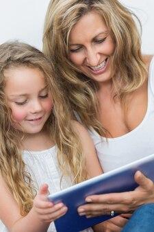 Мать и дочь весело с планшетным компьютером