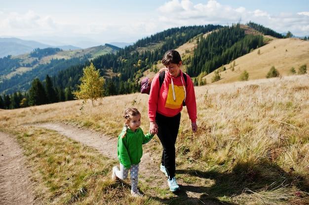 山での母と娘のハイキング。家族旅行、冒険、観光の概念。屋外でのライフスタイルの秋の休暇。