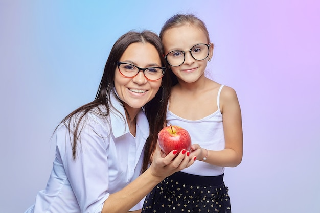 母と娘は手に大きな赤いリンゴを握る