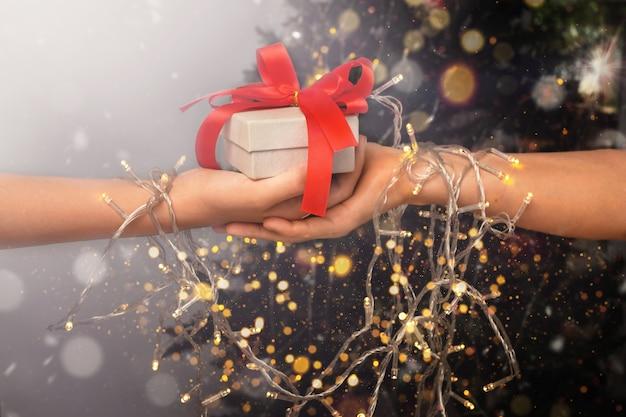 Мать и дочь держат подарочную коробку вместе с рождественскими огнями