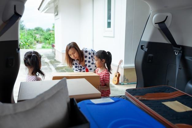 Мать и дочь держат и несут картонную коробку с вещами, вместе движущимися в машину