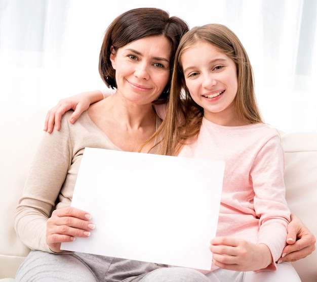 家で手で空の空白の紙を保持している母と娘