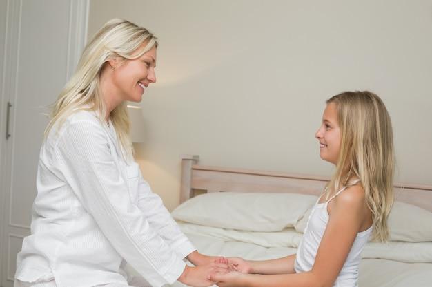 母と娘はベッドの中に手を持っています