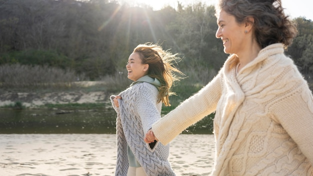 Мать и дочь, взявшись за руки на пляже