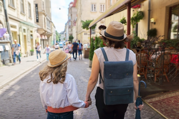 Мать и дочь, держась за руки, гуляют в старом туристическом городе