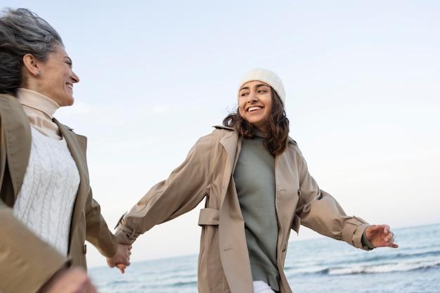 Мать и дочь, взявшись за руки на пляже вместе