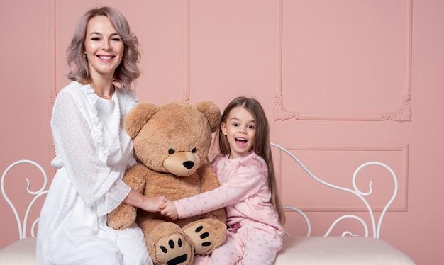 Мать и дочь держат плюшевого мишку