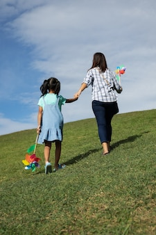 Мать и дочь держат игрушку-турбину и держатся за руку, поднимаясь на вершину холма