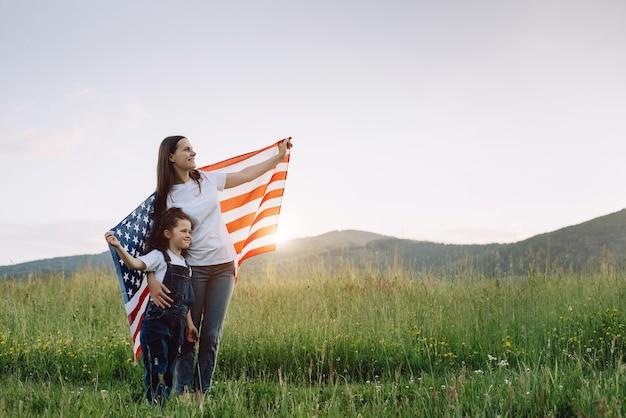 엄마와 딸이 미국 국기를 들고 있다