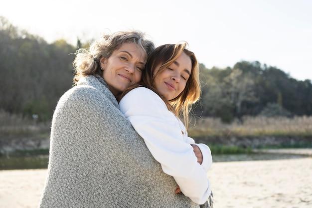 Мать и дочь обнимают друг друга на открытом воздухе на пляже