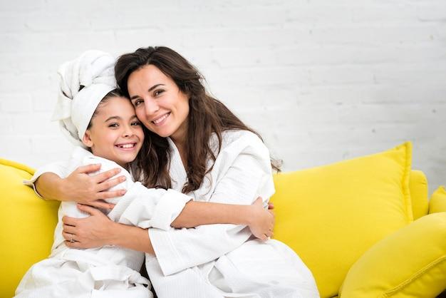 Мать и дочь обнимаются в мантии
