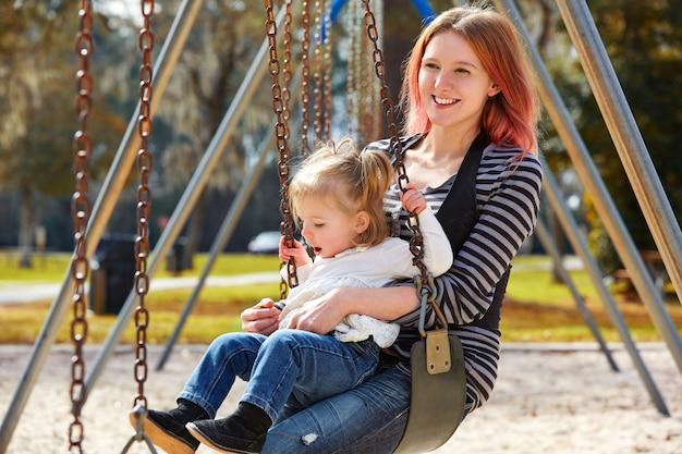 Мать и дочь на качелях в парке