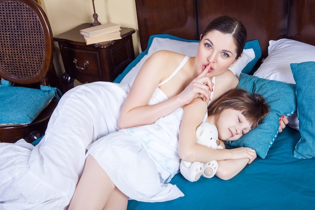 寝室の母と娘。カメラでハッシュサインを示している母親、目を閉じて眠っている娘。スタジオショット