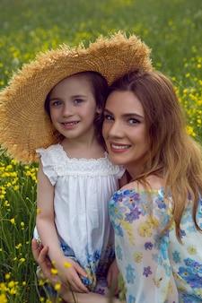 夏の日の黄色い花畑にドレスと帽子をかぶった母と娘が立つ
