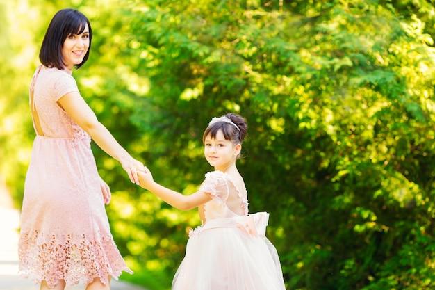 晴れた日には、お祝いのドレスを着た母と娘が公園を散歩する
