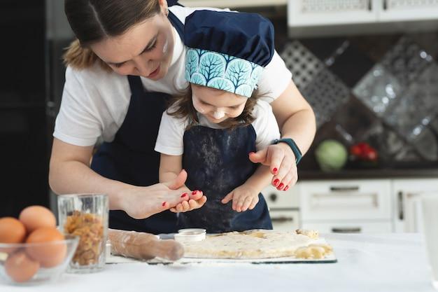 同じエプロンとシェフの帽子をかぶった母と娘がキッチンで調理する