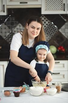 同じエプロンとシェフの帽子をかぶった母と娘がキッチンで料理をする
