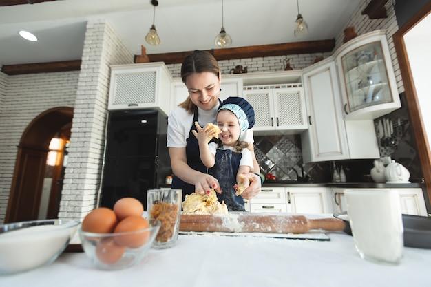Мать и дочь в одинаковых фартуках и поварской шляпе готовят на кухне