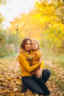 Мать и дочь в парке, полном листьев