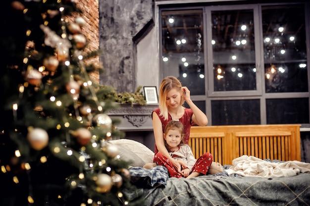 빨간 가족의 엄마와 딸 다락방 인테리어 집에서 새해 나무 근처에 침대에 함께 앉아 잠옷을 봐