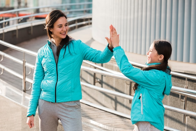 Мать и дочь в спортивной одежде высокого fiving