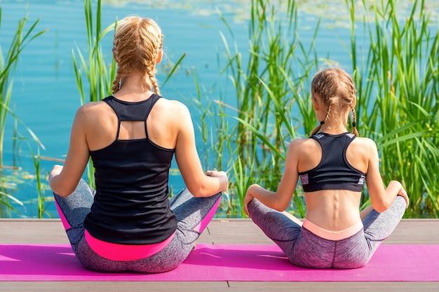 야외 물 근처 부두에 매트에 앉아 운동복에 엄마와 딸