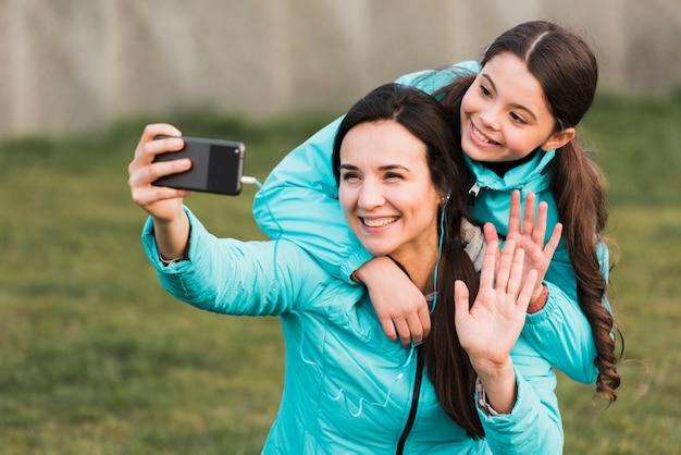Мать и дочь в спортивной одежде, принимая селфи