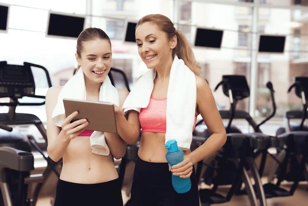 체육관에서 태블릿을 사용하여 운동복에 어머니와 딸