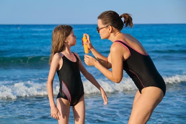 해변에서 수영복을 입은 엄마와 딸, 부모는 선 스크린 크림을 적용합니다.