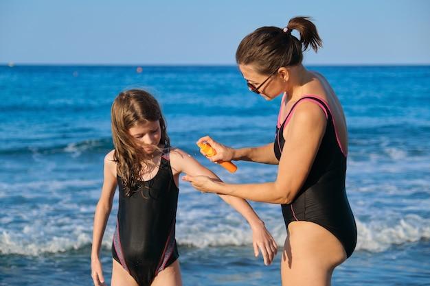 어머니와 딸이 해변에서 수영복, 부모는 자외선 차단제를 적용합니다.