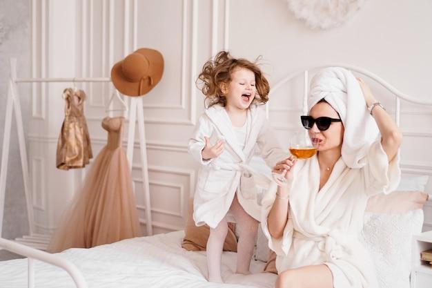 バスローブを着た寝室の母と娘幸せな娘がジャンプしています