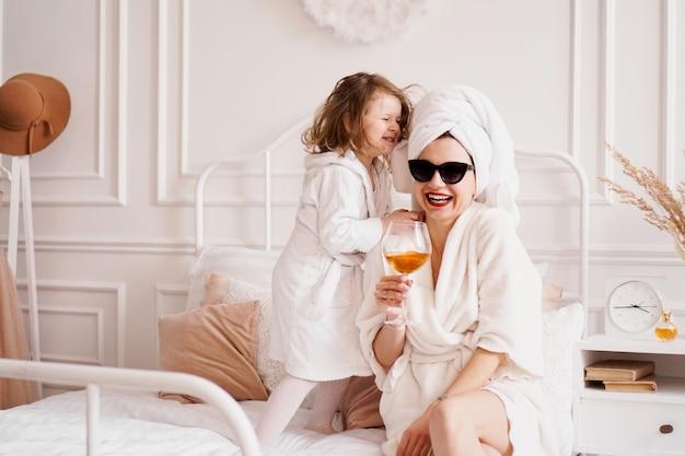 Мать и дочь в спальне в халатах счастливая дочь прыгает
