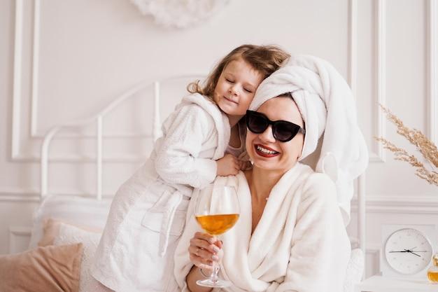 バスローブを着た寝室の母と娘、女の子は彼女のお母さんを抱きしめます