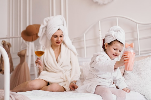 バスローブを着た寝室の母と娘
