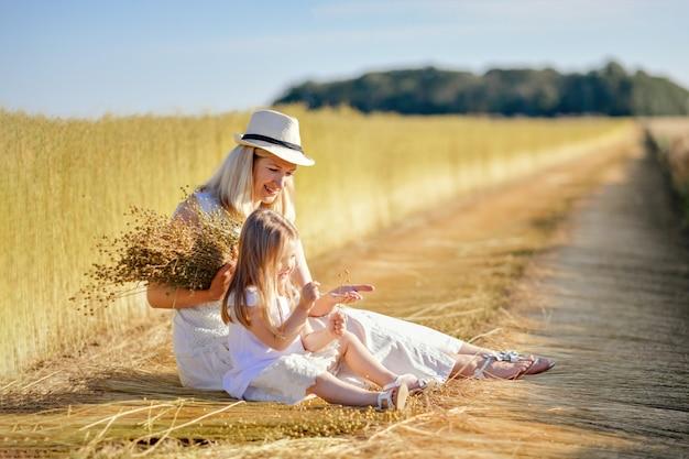 亜麻を収穫しながら畑にいる母と娘