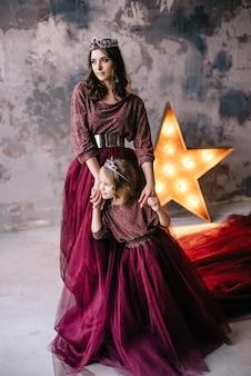 女王と王女をイメージした母と娘がマルサラの色のドレスを着て、ロフトに長い電車があります