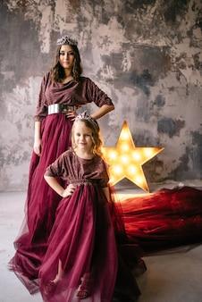 女王と王女をイメージした母と娘が、ロフトに長い電車でマルサラの色のドレスを着ています