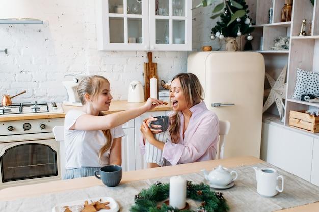 크리스마스와 새해를 위해 꾸며진 부엌에서 어머니와 딸, 차 또는 코코아를 마시고, 대화를 나누고, 손님을 기다리고 있습니다.