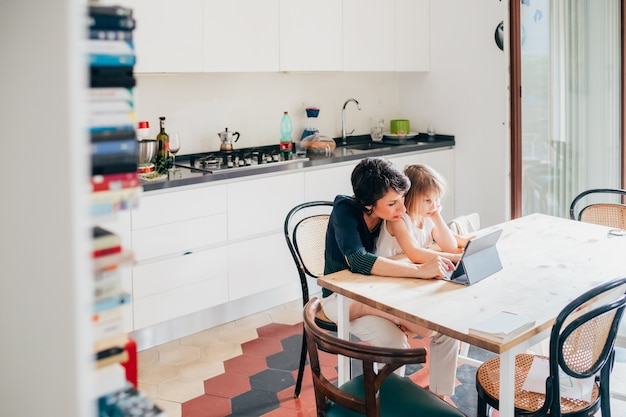 엄마와 딸 실내 태블릿 앉아 테이블을 사용 하여