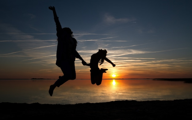 Мать и дочь прыгают силуэт
