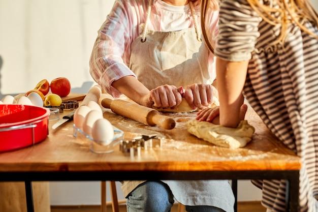Мама и дочь замешивают тесто для домашнего десерта на кухне, учат и учат
