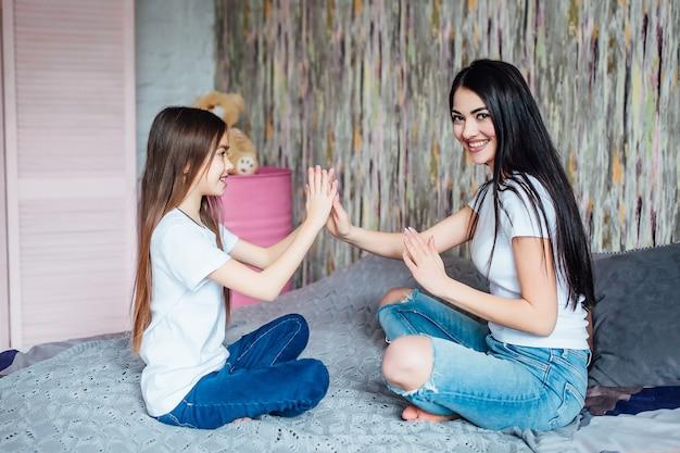 엄마와 딸이 침대에 누워 있습니다. 재미. 서로를 바라보는 가족의 날