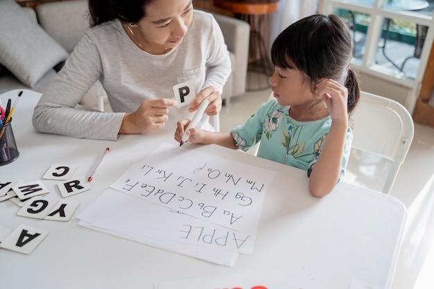 집에서 편지를 읽고 쓰는 법을 배우는 엄마와 딸