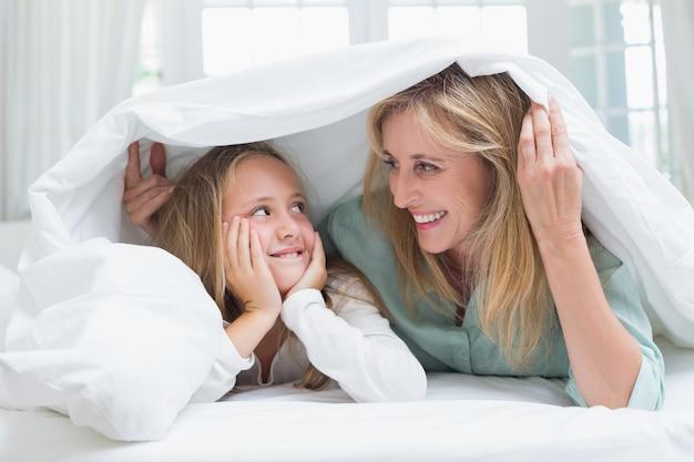 母と娘が羽毛布団の下でお互いを見て