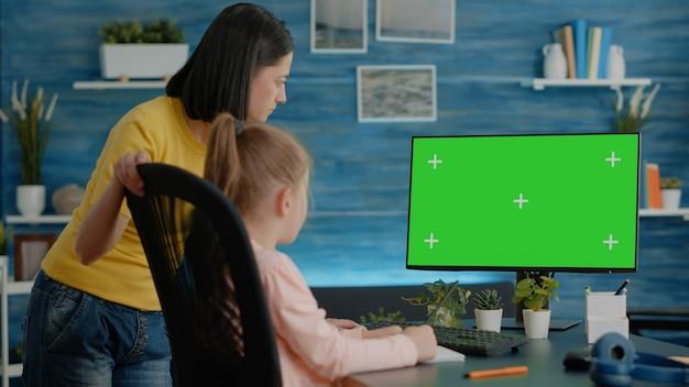 コンピューターで水平方向の緑色の画面を見ている母と娘