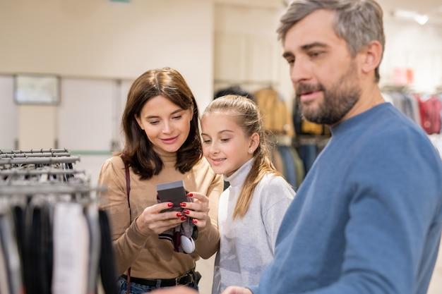 セール中に新しいカジュアルウェアを選びながら、冬の暖かいニット手袋の価格を見る母と娘