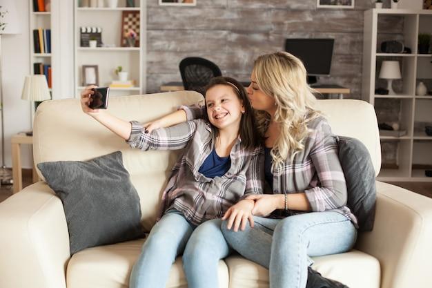 母と娘が携帯電話のカメラをのぞき、アパートのソファに座って自分撮りをしている。