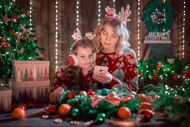 母と娘がクリスマスツリーの横にある携帯電話を見て、オンラインショッピングをしています。