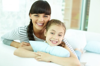 Mother and daughter lying down on bed