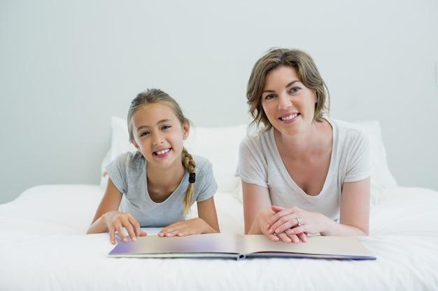 Мать и дочь, лежа на кровати и читая книгу в спальне дома